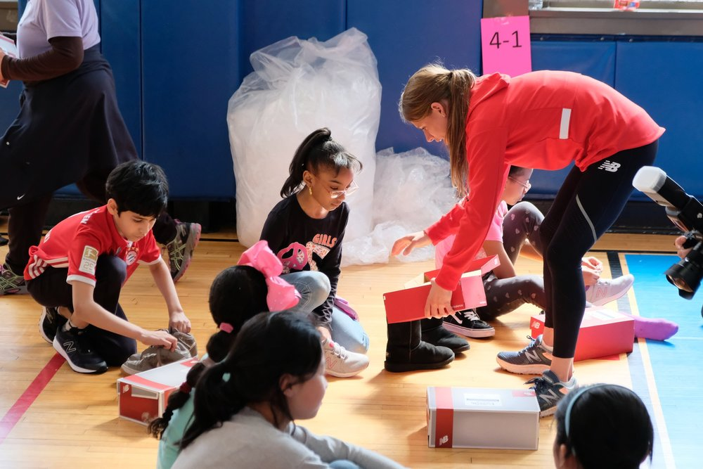 Team New Balance athlete Liz Costello hands out new shoes to fourth and fifth grade students at P.S. 001 in Manhattan.