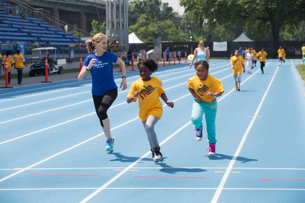 Mary Wittenberg runs with students at a National Running Day celebration at Icahn Stadium.