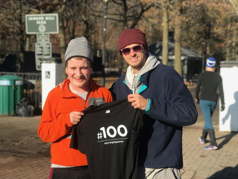 Bryce (left) receives his #100 shirt from NYRR Open Run Program Manager Michael Scher.