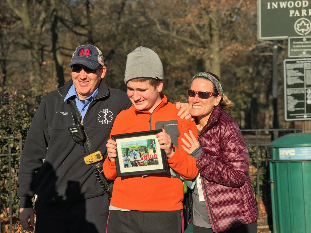 Bryce, with parents Rob Walsh and Jennifer Cameron, receives a commemorative #100 photo from the Inwood Open Run community.