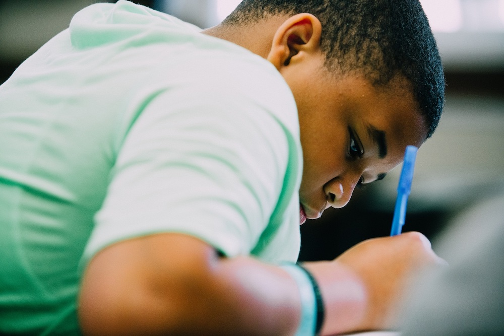 Young African American boy writing at a school desk.jpg