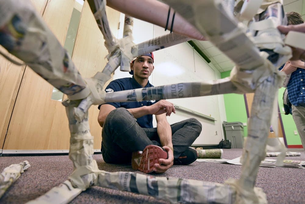 Design team instructor Cody Nelson watches the progress of his team's newspaper tower at the Science Museum of Minnesota in St. Paul on a recent Saturday. Nelson, who served time in prison for manslaughter, turned to prevention programs to steer himself away from gangs and violence. Richard Marshall for MPR News