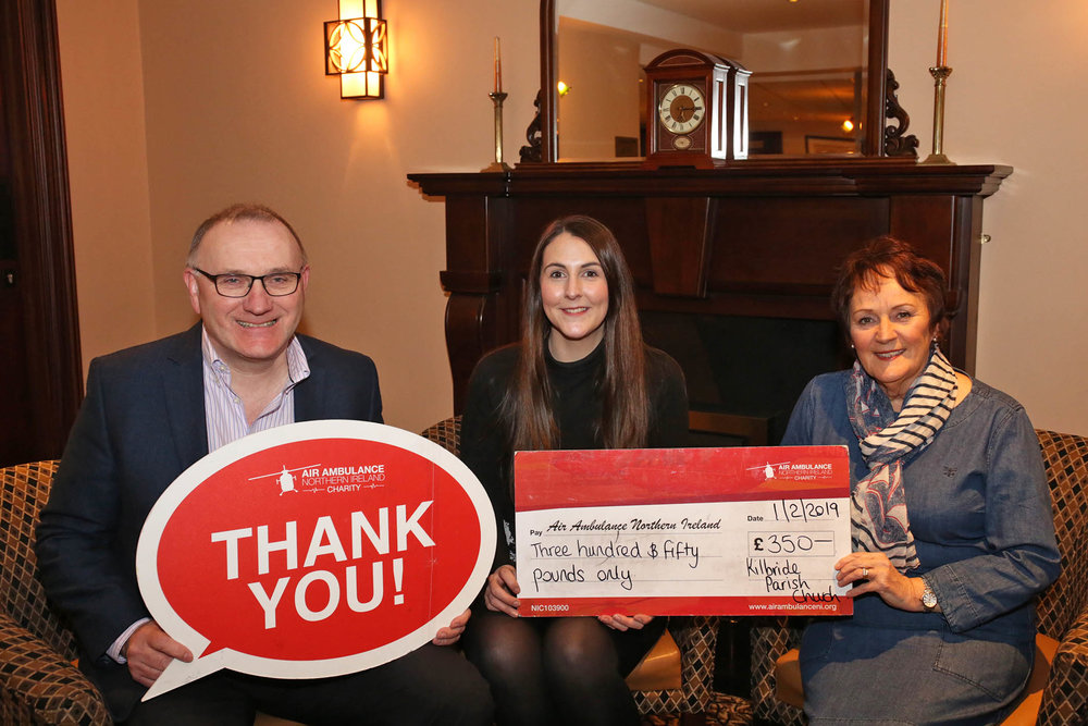 Grace Williams, Air Ambulance NI, receives a cheque from Kate Henry and David Holmes.