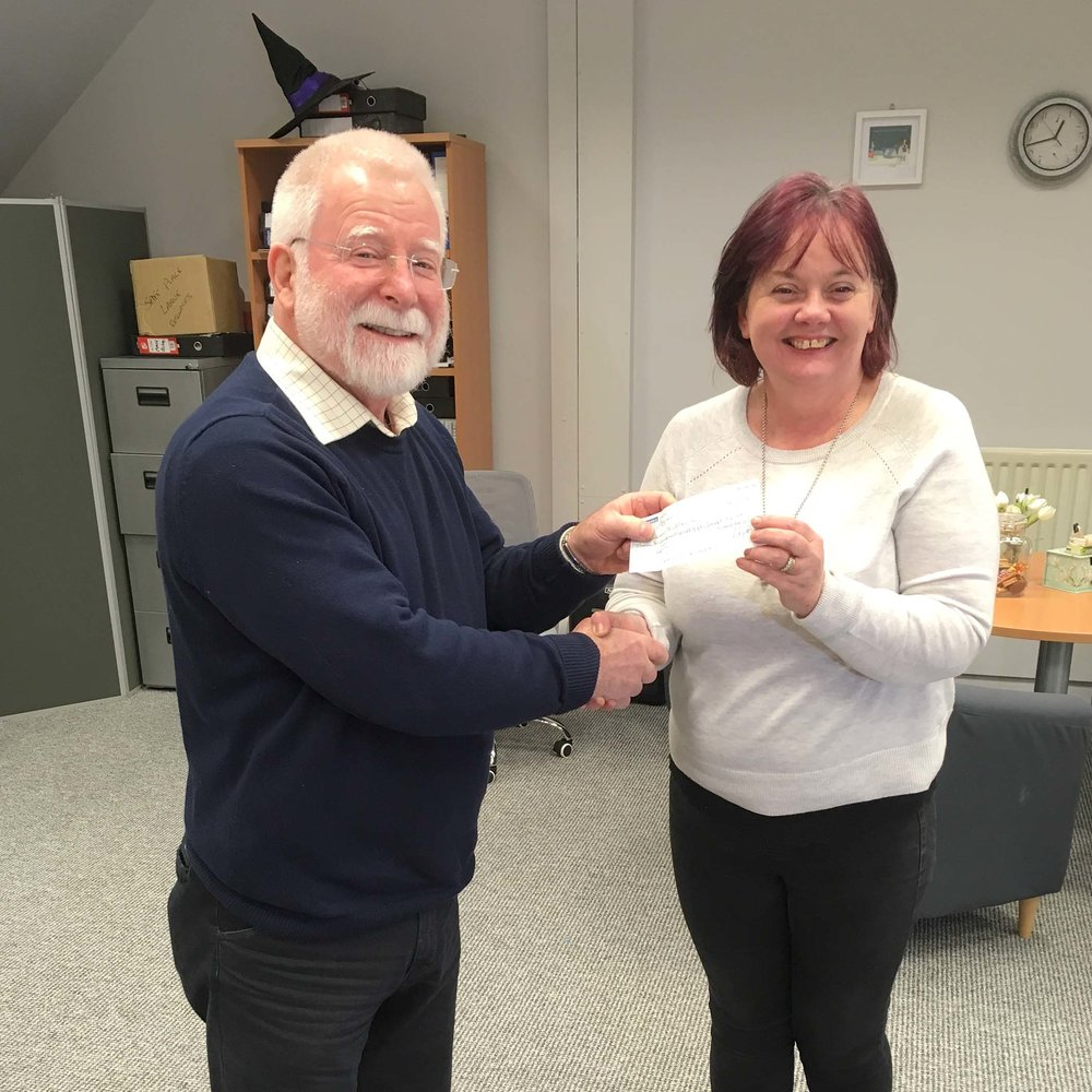 Ivan makes the presentation to staff member Fay Tilson, Women's Aid, in their Larne office.