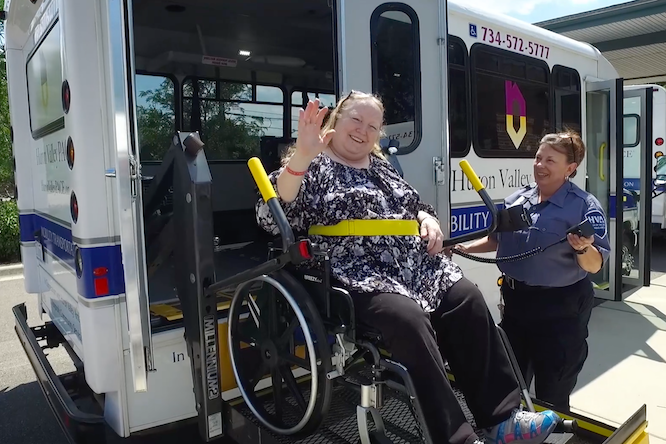Patient in wheelchair waiving while being loaded onto bus