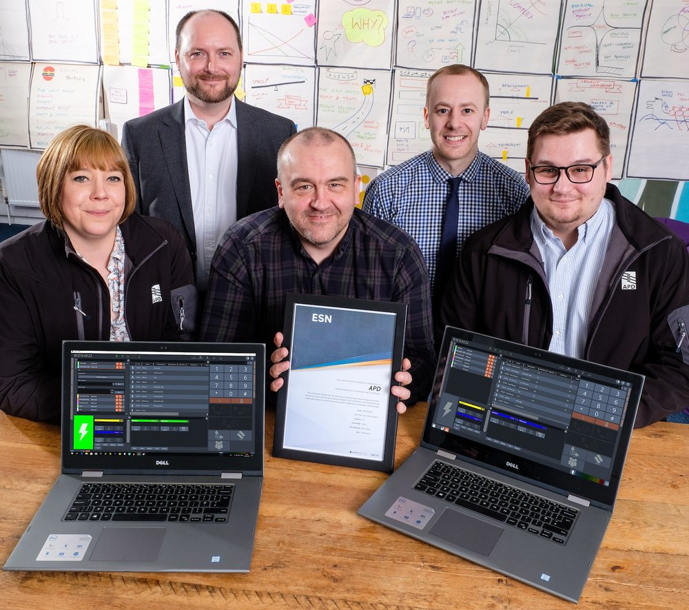 APD Communications Managing Director Mike Isherwood, back left, with members of the ESN Development Team – Technical Manager and ESN Lead Sean Hancock, back right, and, from left, Keeley Barrick, Darren Jackson and Declan Whiting, with the National Approval Testing Service (NATS) certificate.