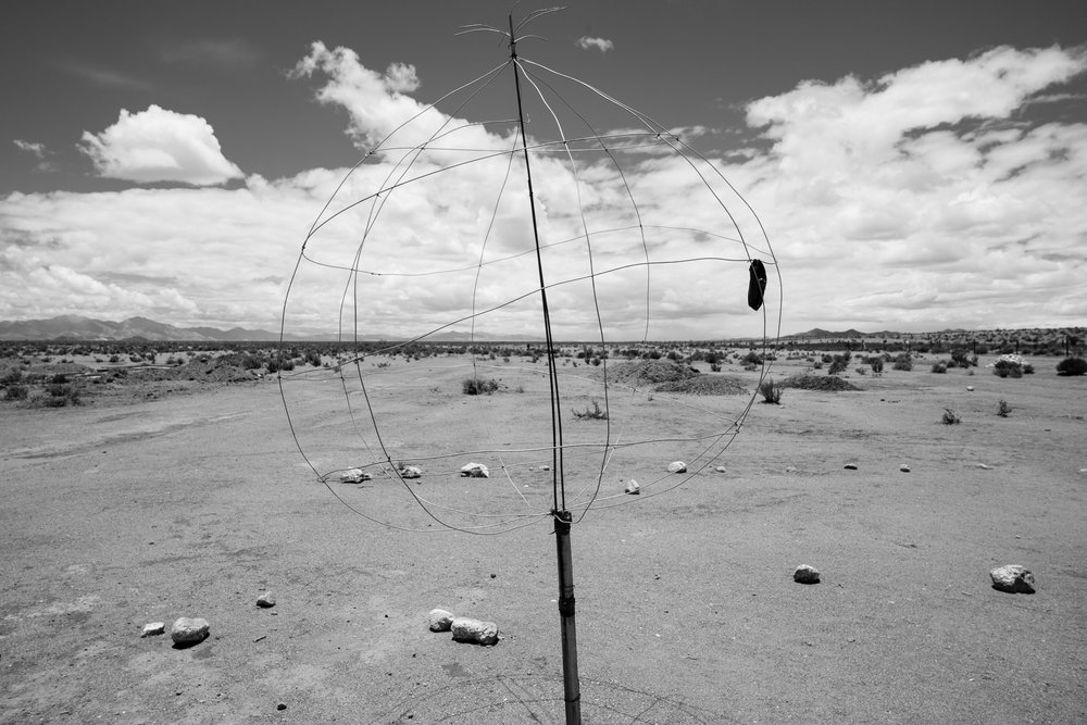 A cell phone hangs off a wire globe, the only way to get cell phone reception in this remote area.