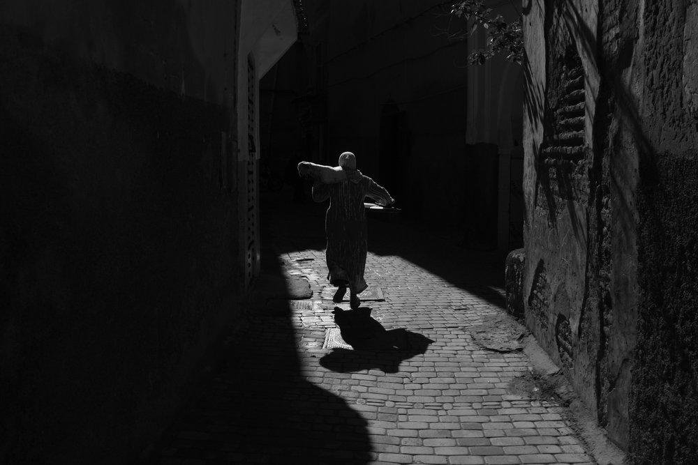 A women delivers bread.Marrakesh, Morocco.