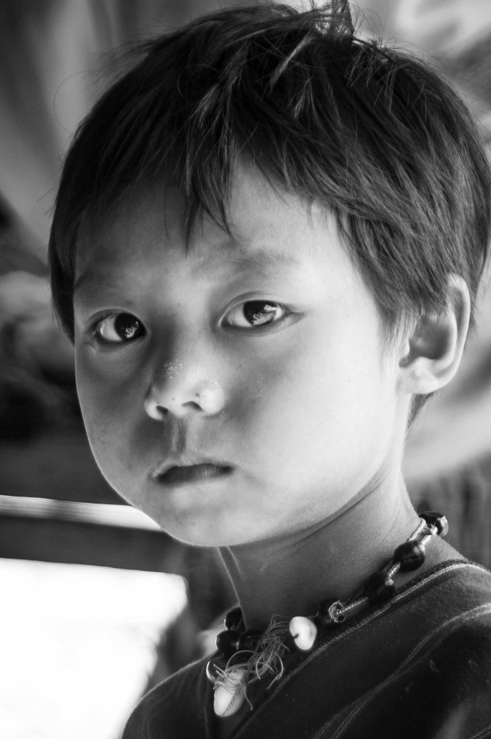 A village elder's grandchild. Northern Thailand.