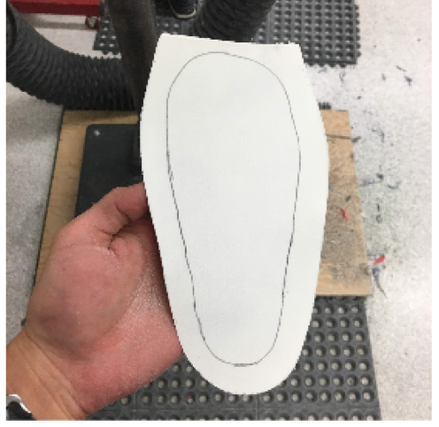 Grab your posting material, place under the device and trace around. Cut the material approximately ¾ of an inch outside of this traced line to provide enough length when folding over the apex of the device, such as the medial arch.