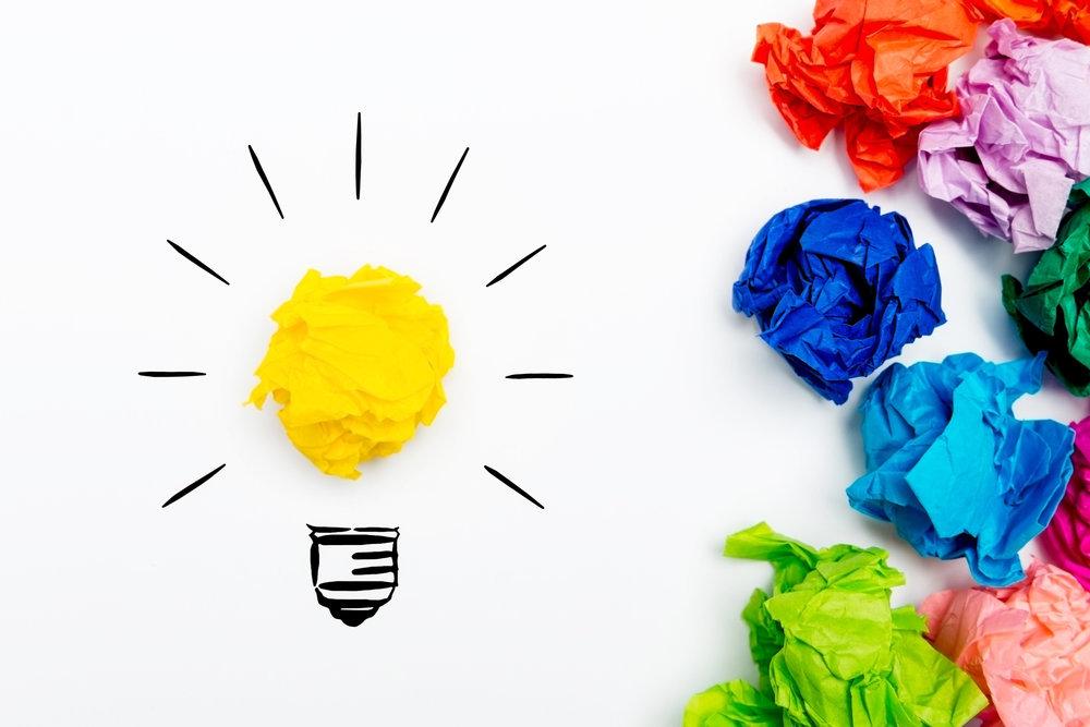 Ny idé! I form av en ritad lysande glödlampa med en gul papperstuss i mitten. Med färgglada papperstussar på sidan om.