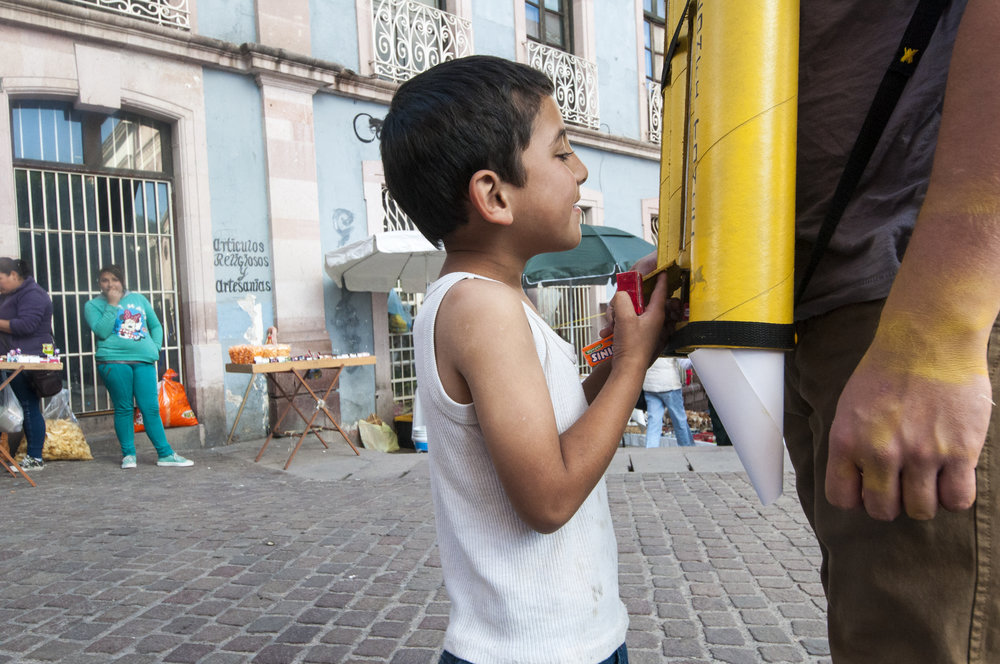 Local Kid interacting with dispenser and Rogelio