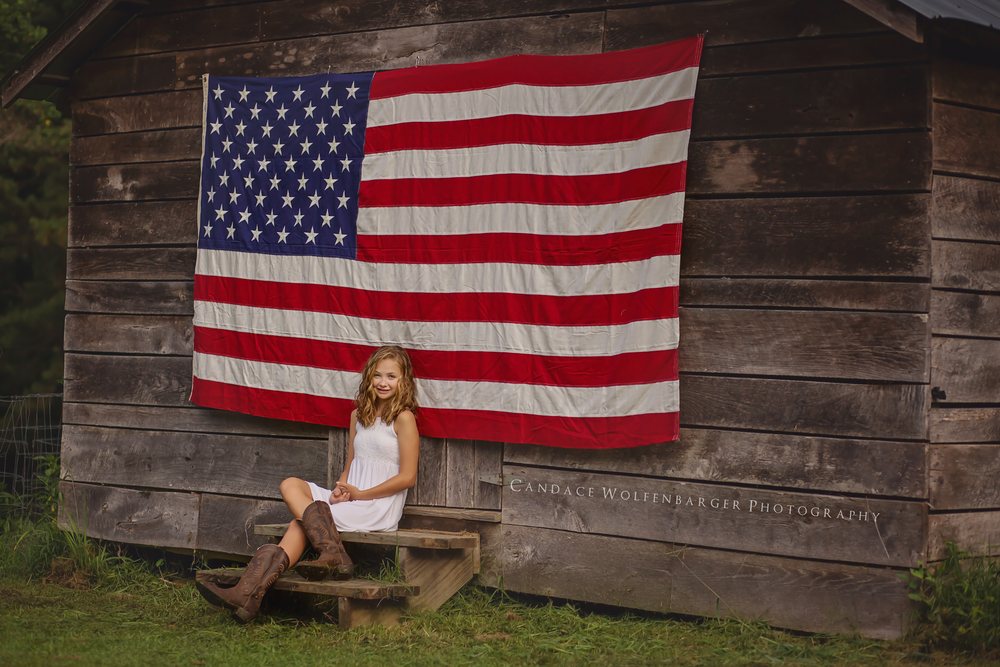 Child sits in front of American Flag for portrait session.