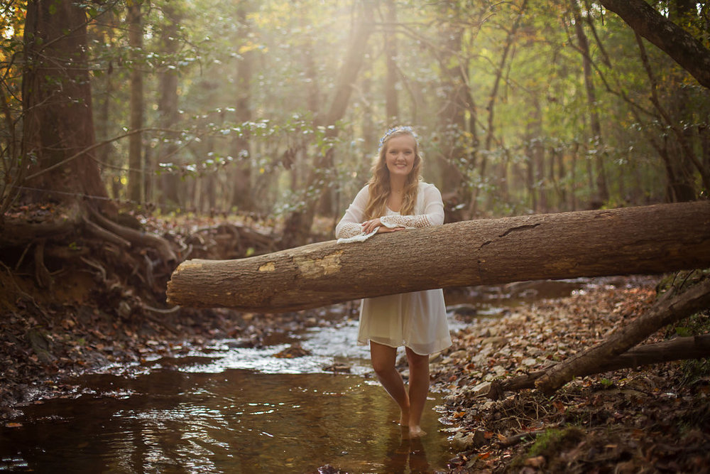 Raleigh NC senior stands behind log in creek bed for senior portraits.