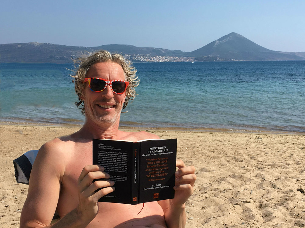 Dr. Bas Bloem enjoying Mentored By A Madman:The William Burroughs Experiment on the beach.