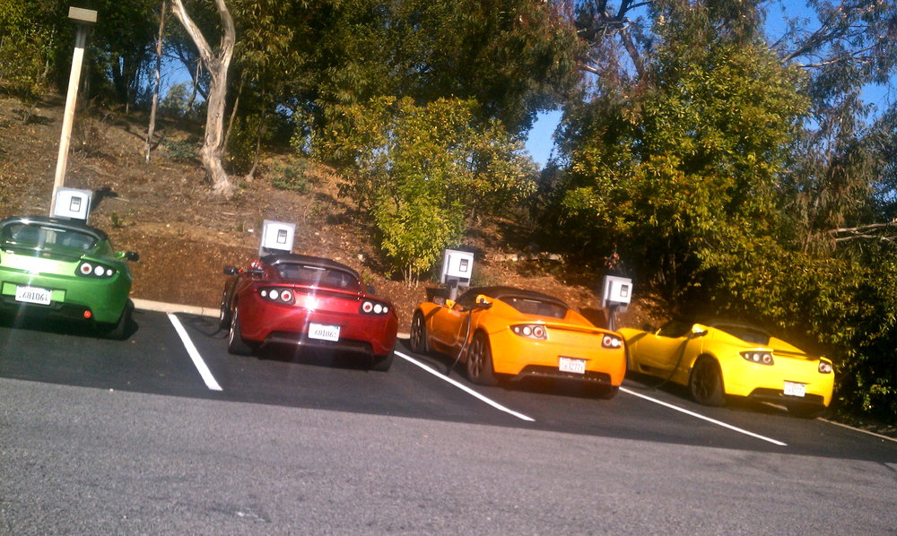 Roadsters lined up at the charging stations outside of HQ.