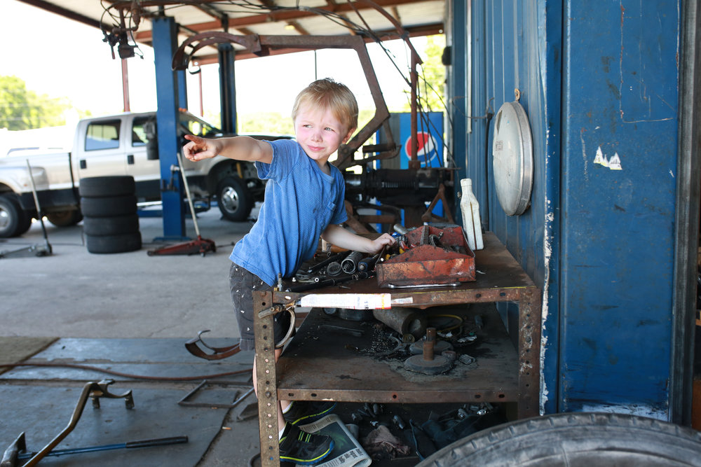 Logan hanging out on the large truck end of the shop playing in the tools.