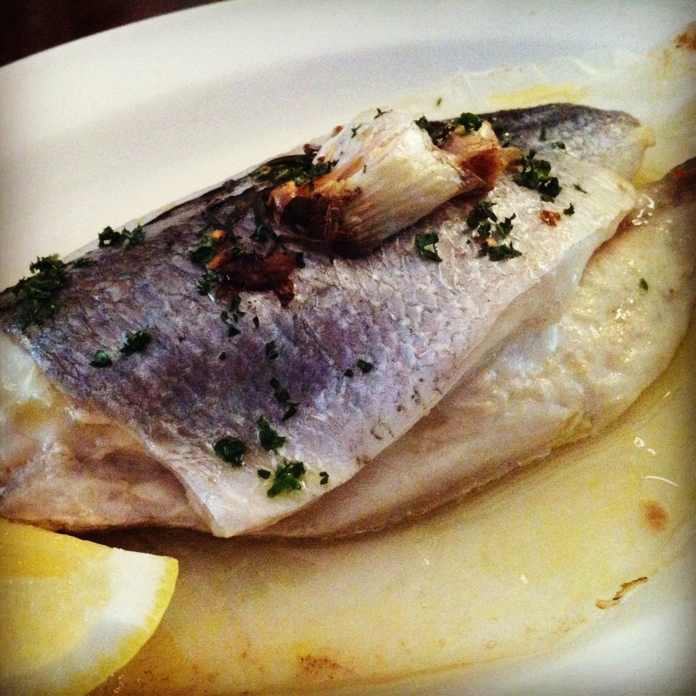 Royal bream baked in paper with garlic, rosemary and chilli