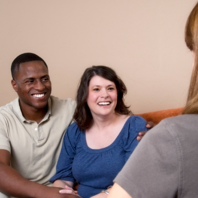 Multi-racial couple receiving marital counseling at Rooted.