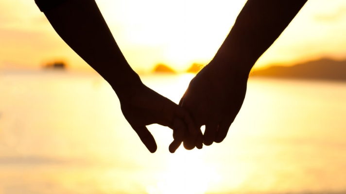 Husband and wife holding hands at the beach, after doing couple counseling with a Marriage and Family Therapist.