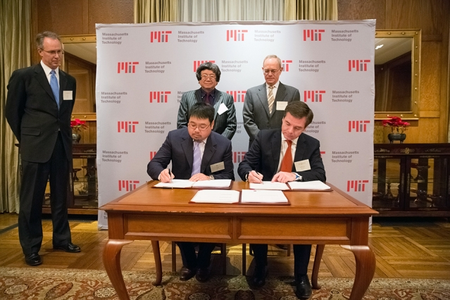 Samuel Tak Lee '62, SM '64 (standing, left) and MIT President L. Rafael Reif look on as Lee's son, Samathur Li, and MIT Executive Vice President and Treasurer Israel Ruiz sign documents related to Lee's $118 million gift to MIT. Image: Bryce Vickmark