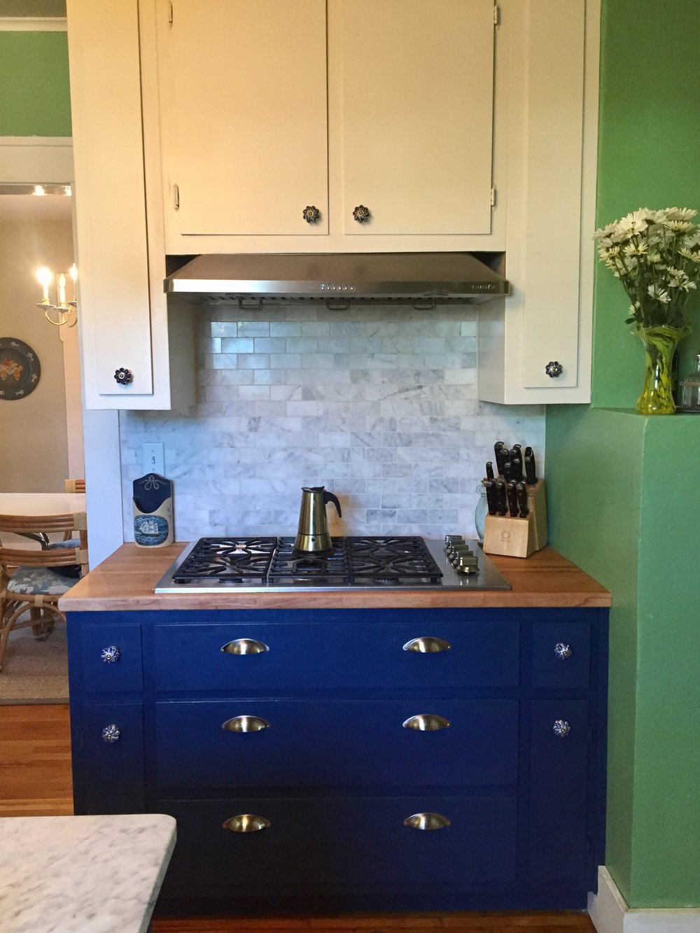 stovetop-spiceracks-marble-backsplash-stainless-steel-hood-cobalt-blue-cabinetry