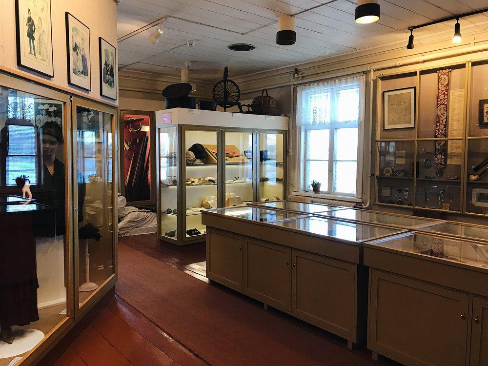 Pakkahuoneen yläkerrasta löytyy runsaasti yhteiskuntahistoriallista esineistöä ja esimerkiksi 1800- ja 1900-luvun vaatetusta pitsiliinoista kävelypukuihin.