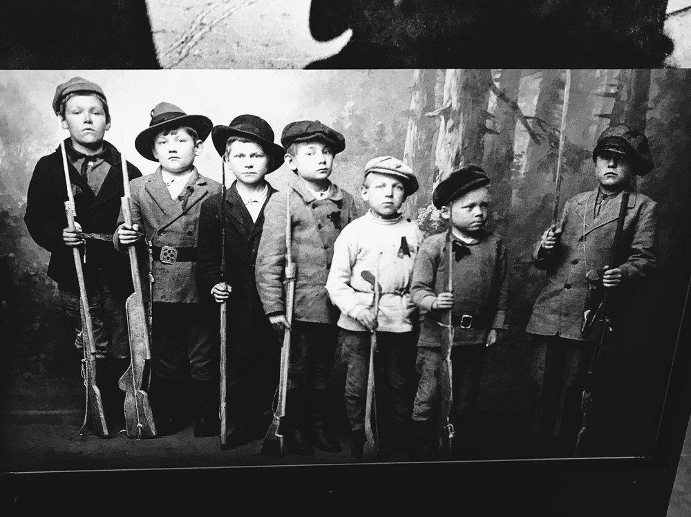 Sata vuotta sitten yhteiskunnalliset jakolinjat ja poliittiset vakaumukset ulottuivat lapsuuteen saakka.Kymin pikkupunakaartilaiset poseerasivat vakavina kameralle vuonna 1918.