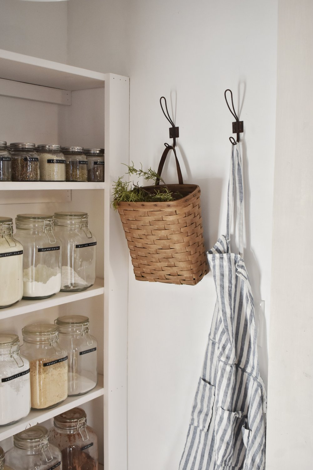 Farmhouse pantry organization for a DiY smal kitchen with walk in pantry. Simple labels on jars with herb basket and linen apron on old hooks.