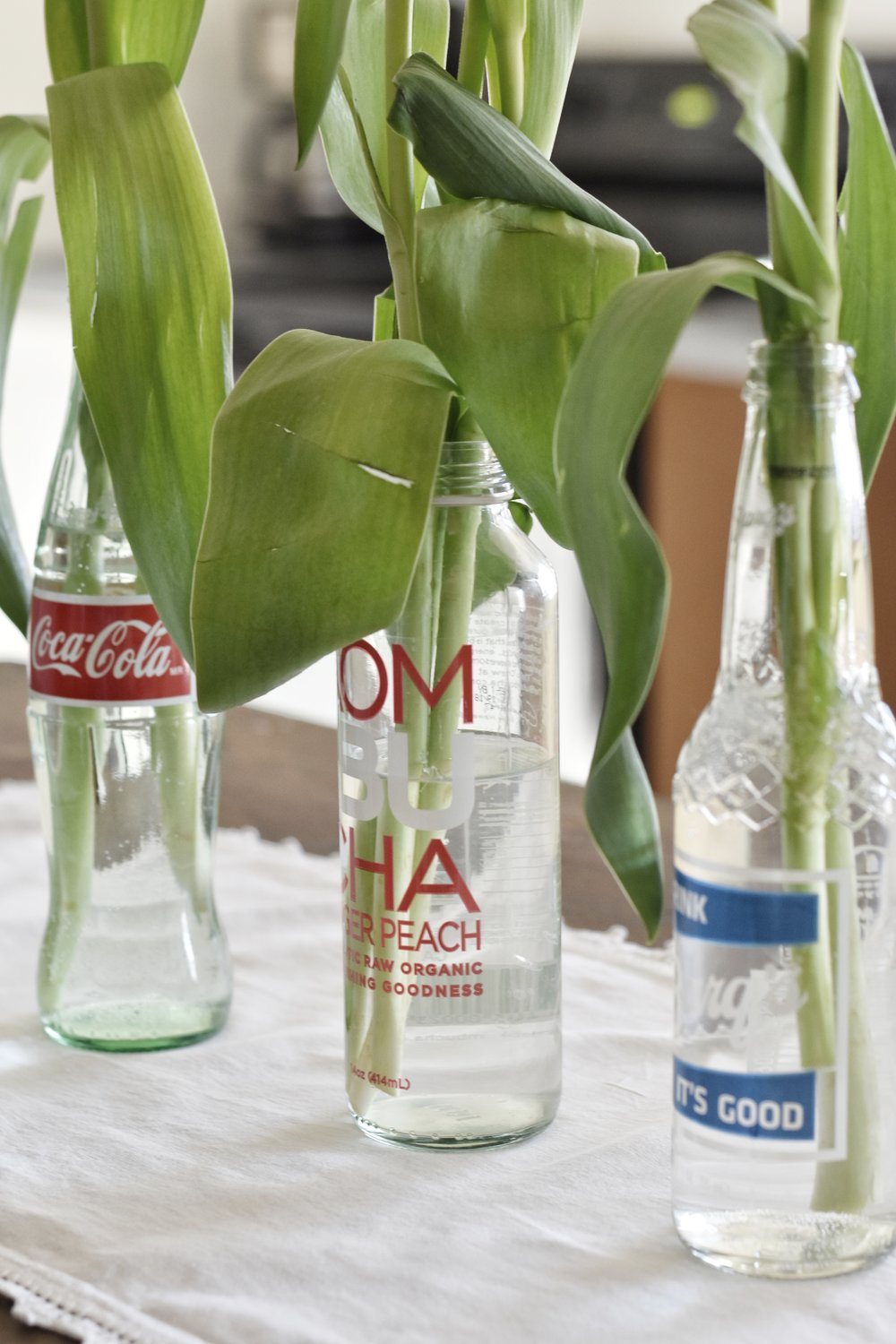Spring centerpiece on a farmhouse kitchen island. Glass soda bottles and white tulips.