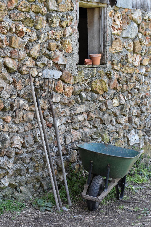 old green wheelbarrow against a stone foundation with old garden tools.   www.rockyhedgefarm.com