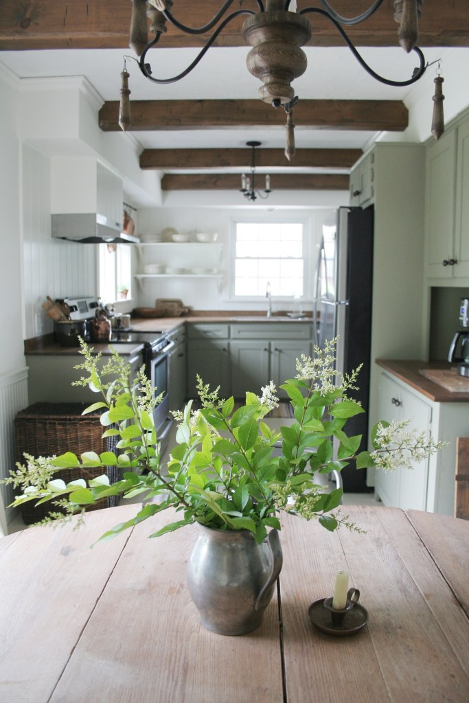 Gorgeous kitchen by @megan.d.miller on Instagram. Simple farmhouse style kitchen with wood beams, White Dove walls and green kitchen cabinents. #farmhousekitchen #simplekitchen #farmhousesimple