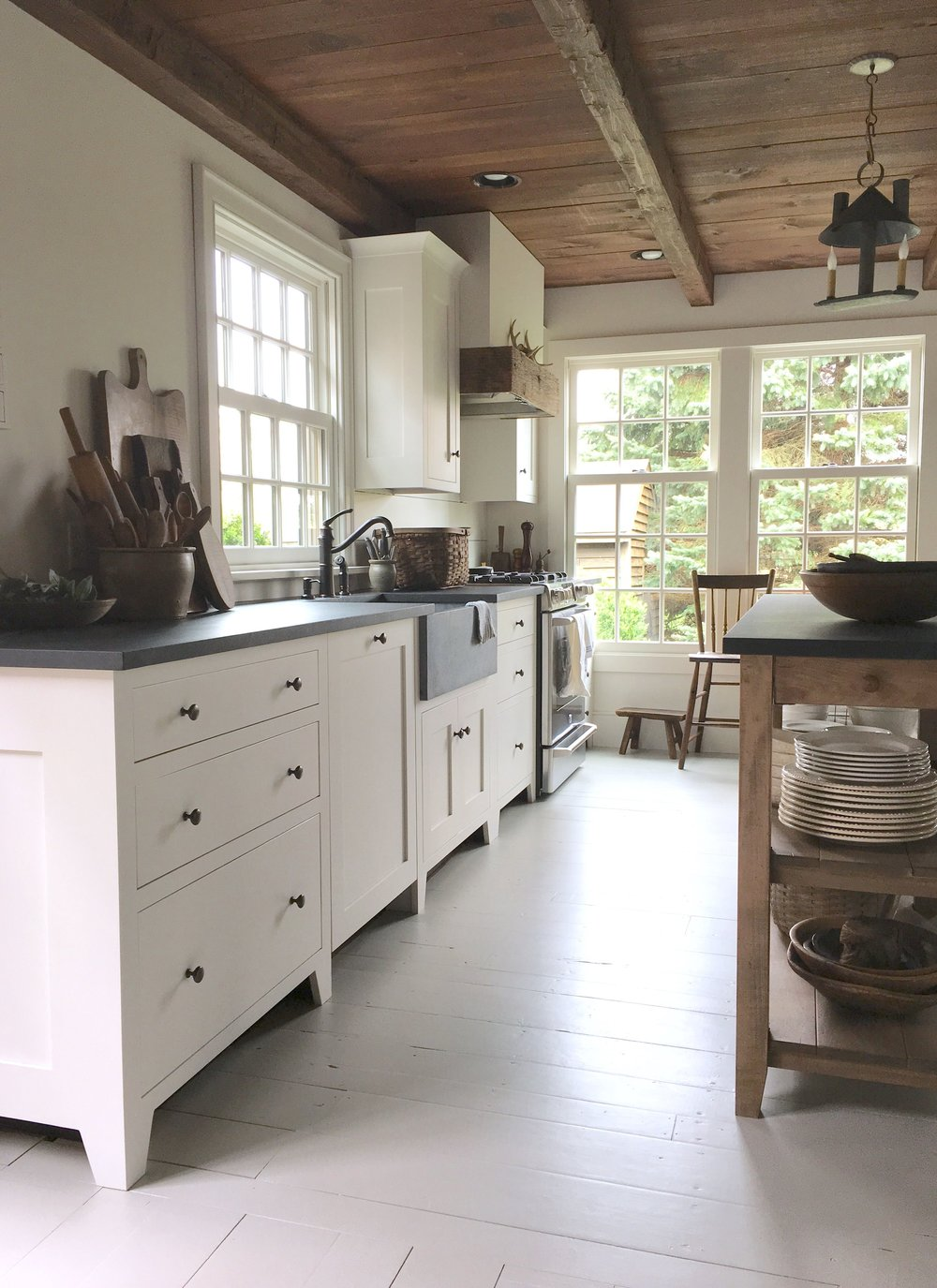 Gorgeous farmhouse and shaker style by the ever so talented Phoebe Troyer. I love the windows, wood ceiling. breadboards, apron sink, black counters, white cabinets and those wood beams on the ceiling.