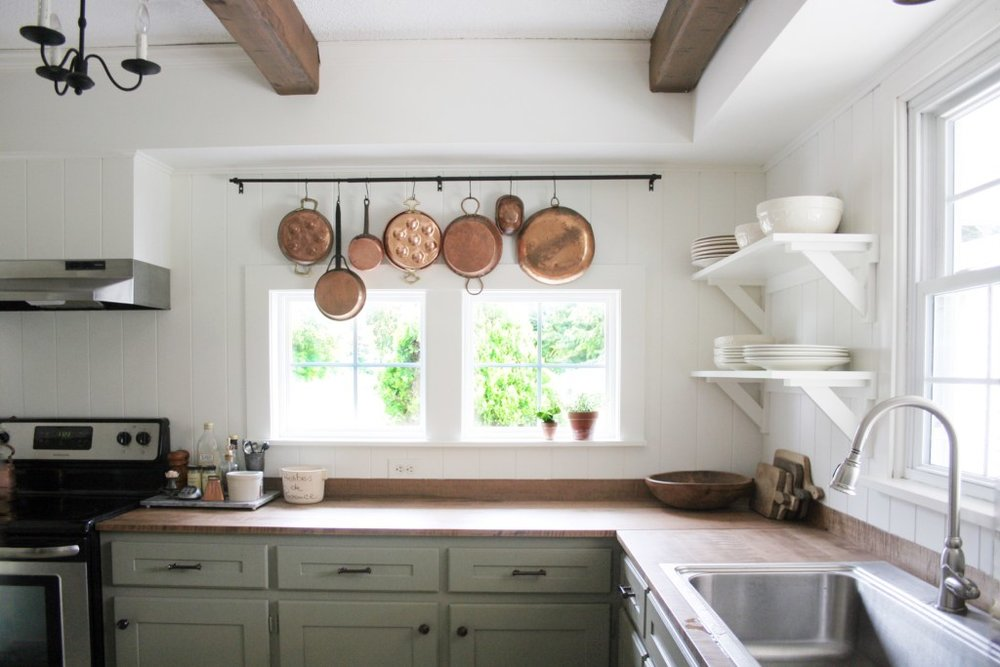 image from Megan.d.Miller of her farmhouse style kitchen makeover. Green cabinets, white dove walls, wood beams.jpeg