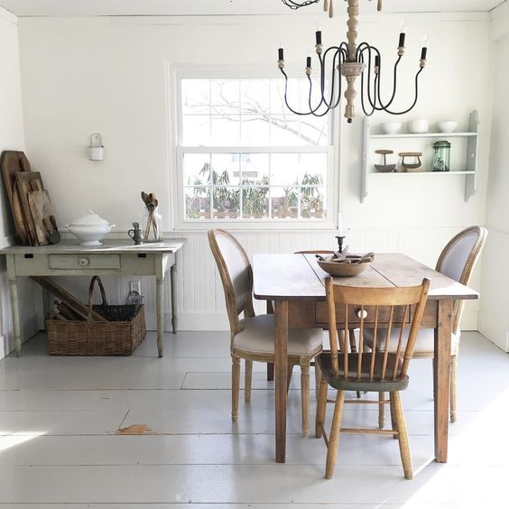 farmhouse dining room by Ellie Campbell with white floors and vintage finds. farmhouse table, wooden chandelier.jpg