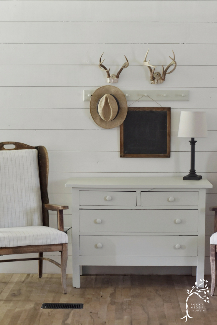 Simple Farmhouse Entry Way that is done in gorgeous neutral colors, wing-back chairs, antlers and has a rustic yet simple farmhouse style