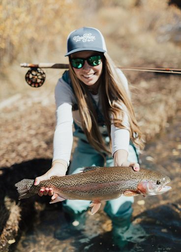 Dakota aka @muddyputty with a beautiful rainbow trout pulled in on a Moonshine Rod and Ross Reel Photo Credit: Black Mountain Cinema