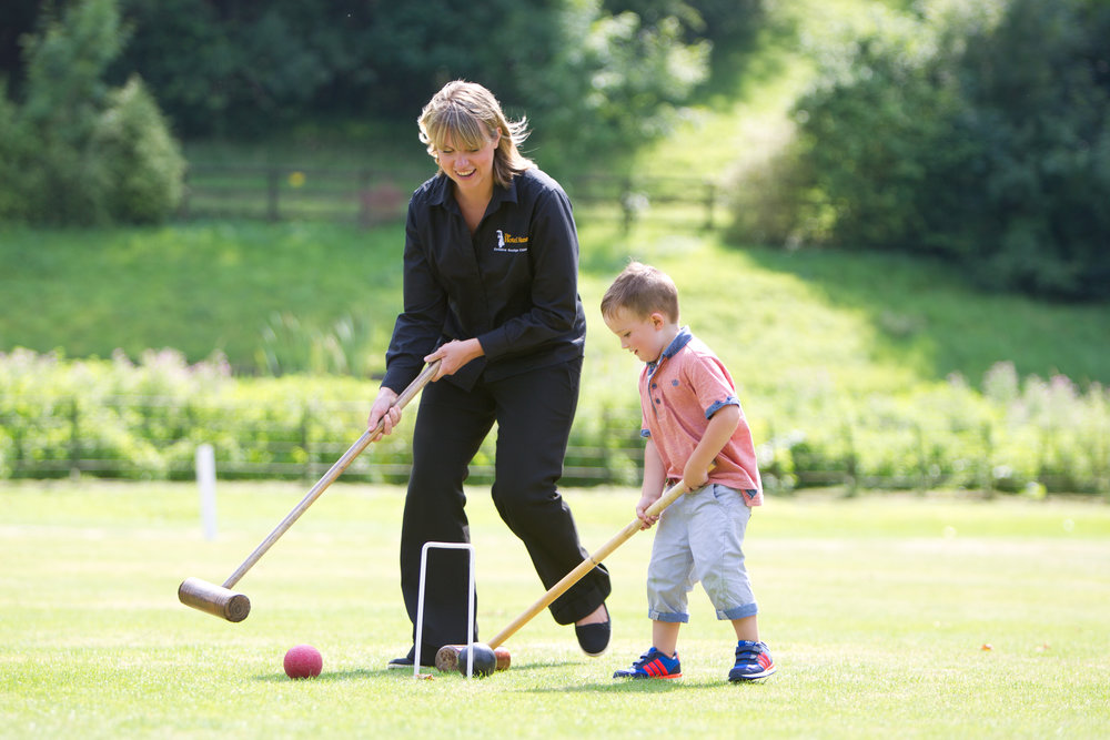 Nanny plays croquet with child