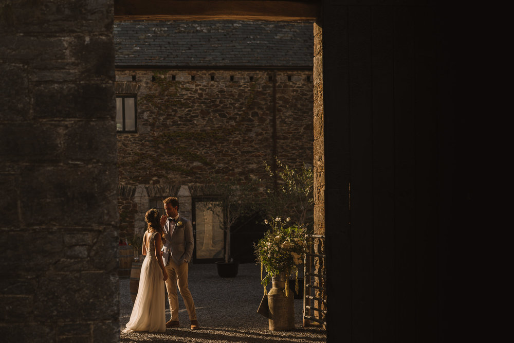 A ninja-like capture of Tara & Sam taking a few moments together before they rejoin their guests. Photographed during their elopement to the  Anrán  in Devon.