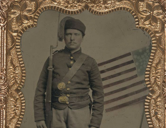 (Unidentified_soldier_in_Union_uniform_with_Zouave_fez_and_bayoneted_musket_in_front_of_painted_backdrop_showing_American_flag)_(LOC)_(5228558775).jpg