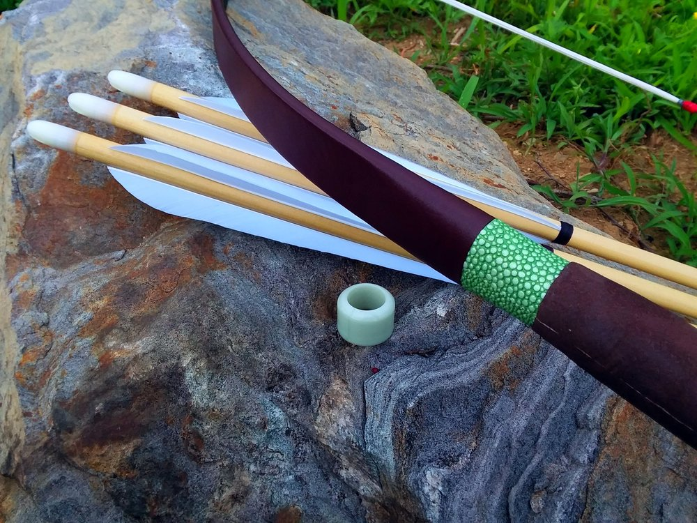 The thick walled version of our Manchu ring, seen here in it's jade-like incarnation. Next to it are some of our Manchu arrows and Jia Zhiwei's Manchu bow with house made arrows and our Manchu ring.