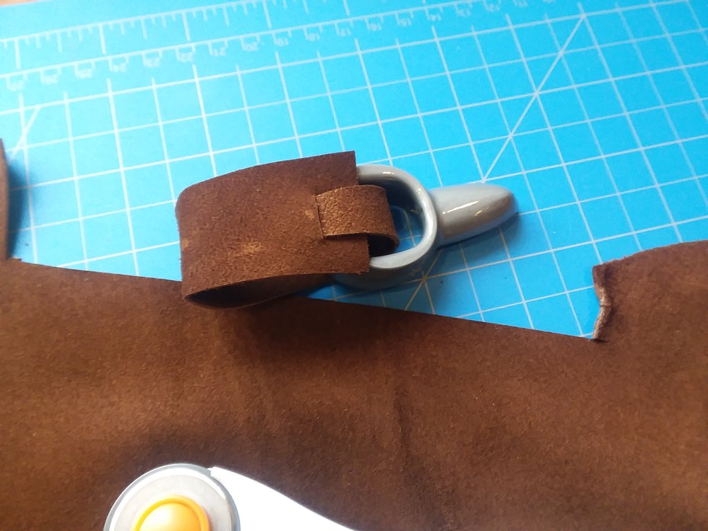 Cut a small slot to insert the narrow end into the wide end. A stitch or leather adhesive will then make it permenant.