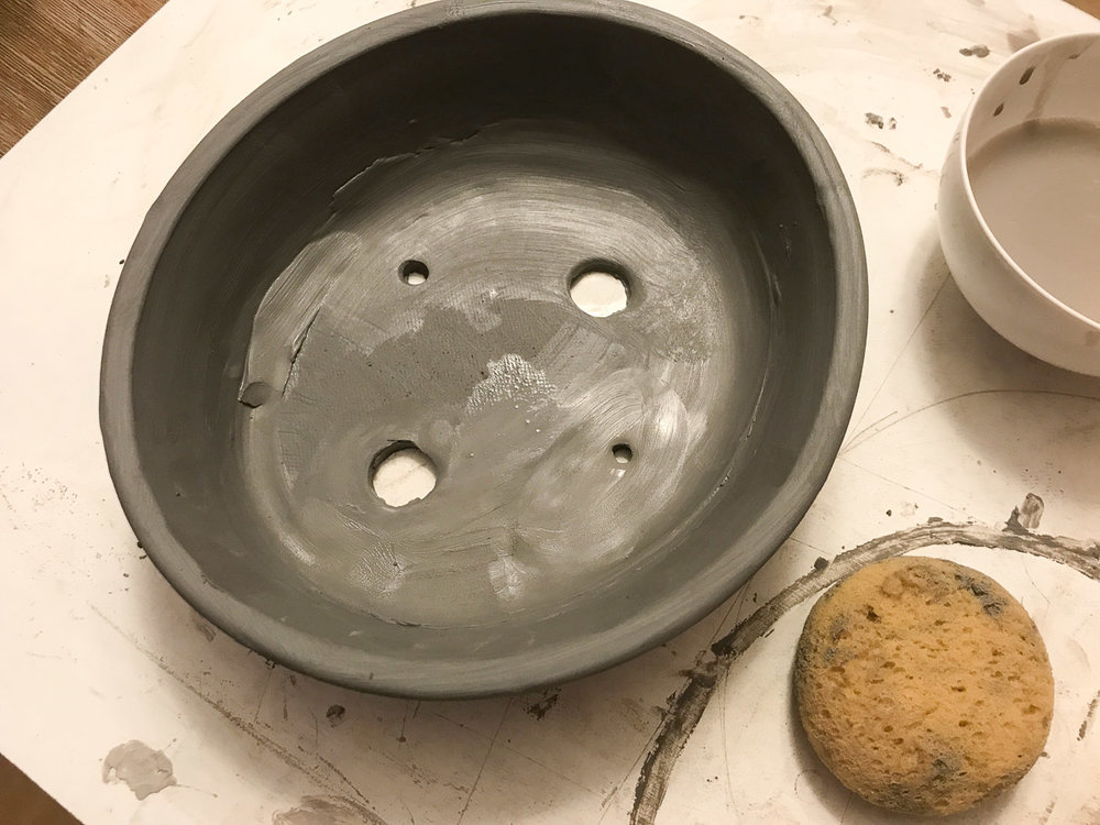 Clay bead being smoothed into the seams of the bonsai pot