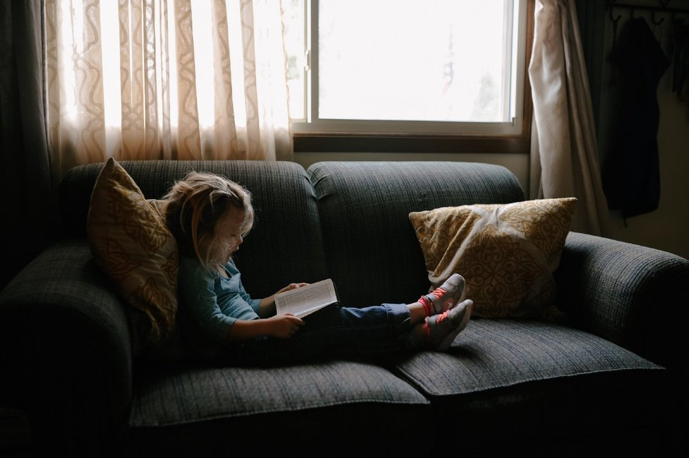 """girl reading book sitting on sofa"" by  Josh Applegate  on  Unsplash"