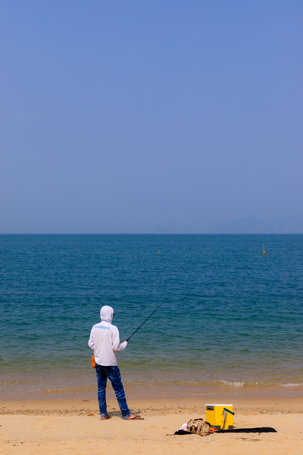 The contrast between the white jacket the fisherman was wearing to ward off the sun, the sand, the sea and the sky just immediately jumped out at me as I walked past. This shot stood out for me as his pose breaks up the horizontal lines given by the shore and the skyline.