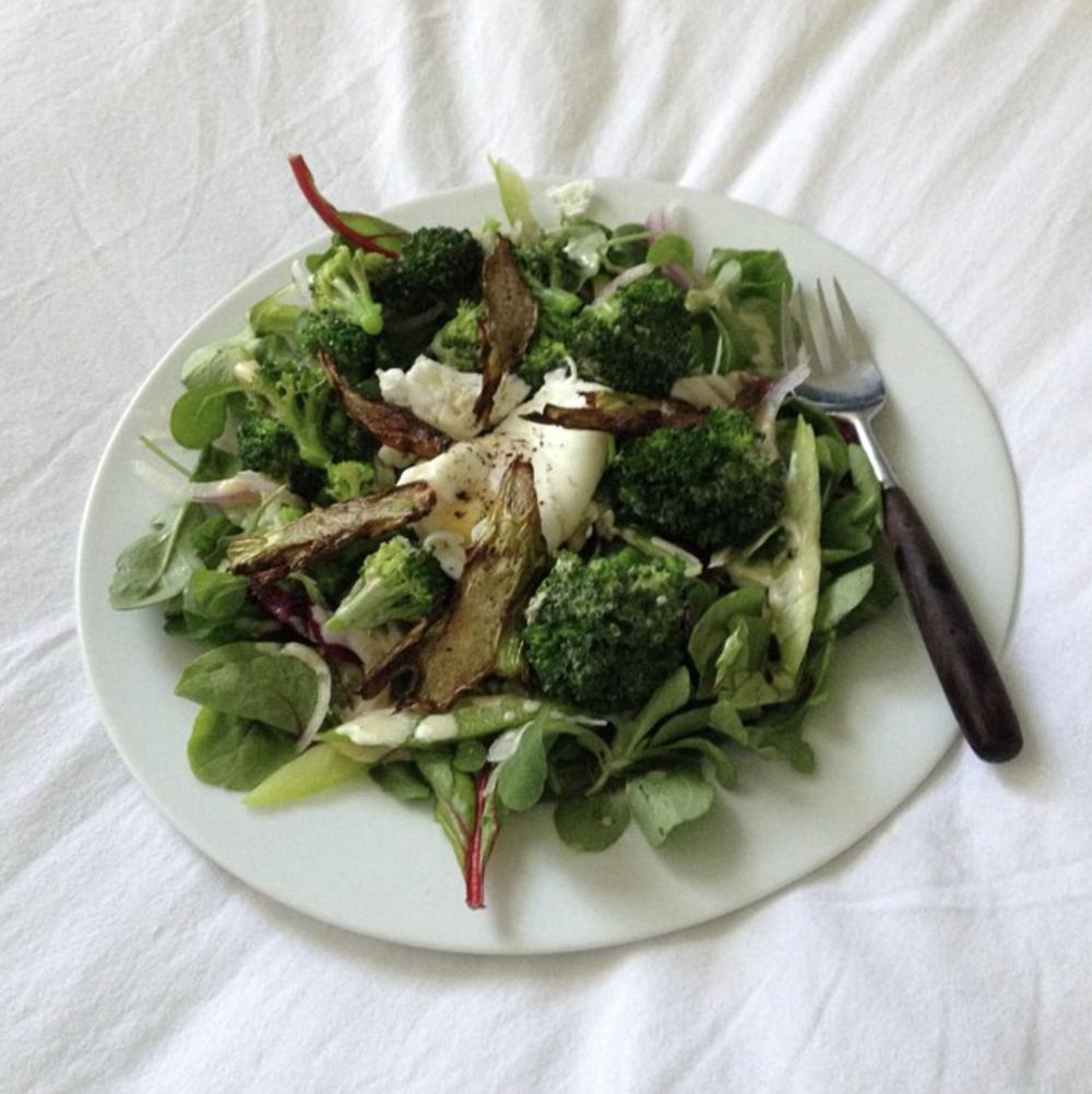 Saut éed broccoli stem and poached egg with steamed florets over greens with a light pine nut, lemon, miso vinaigrette