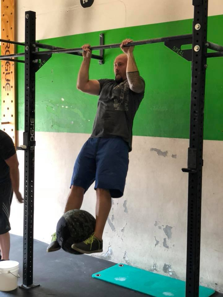 Joe working hard on a strict weighted pull-up