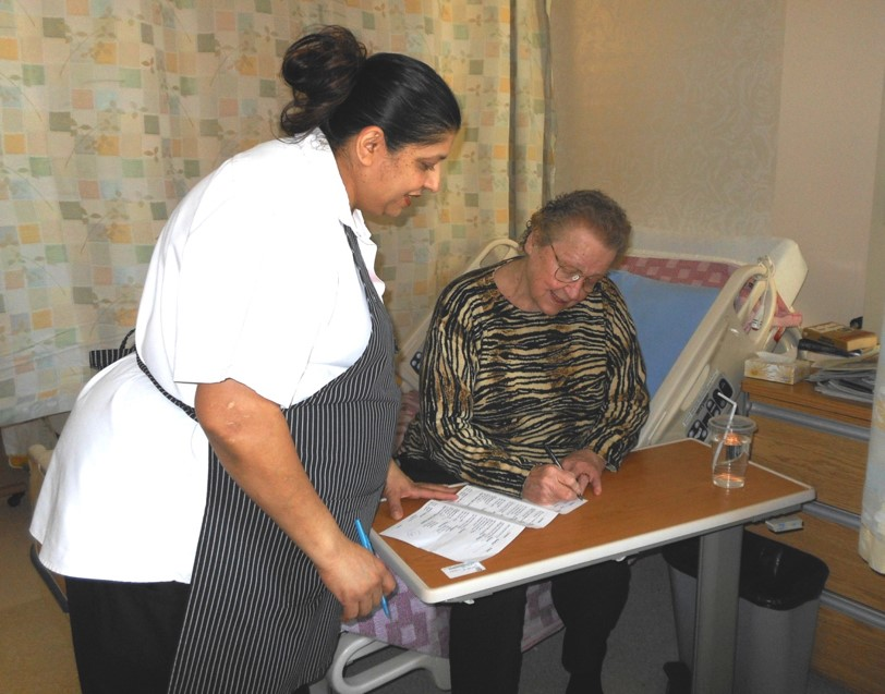 Patient Food Services Worker assists patient to complete their menu selections.