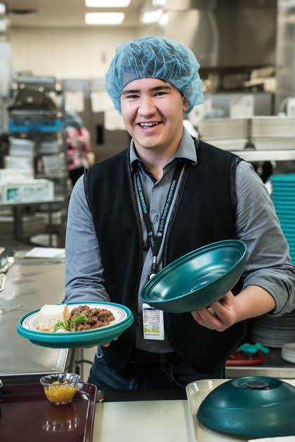 Connor, a staff member showing off traditional food served at Yukon Hospital.