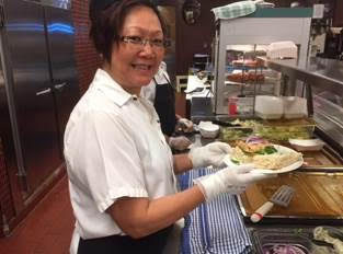 Joyce Wong serving up the salmon on bannock sandwich in the hospital cafeteria
